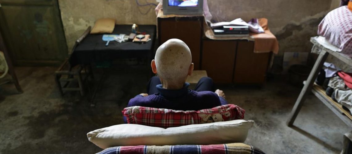 Qin Wenji, 82, who suffers from skin cancer, watches TV in his bedroom at Heshan village, in Shimen county, central China's Hunan Province, June 3, 2014. REUTERS/Jason Lee